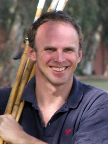 Dan Keating Holding Polo Mallets on His Shoulder
