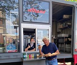 Jay Leno standing next to the A Mano Pizza truck