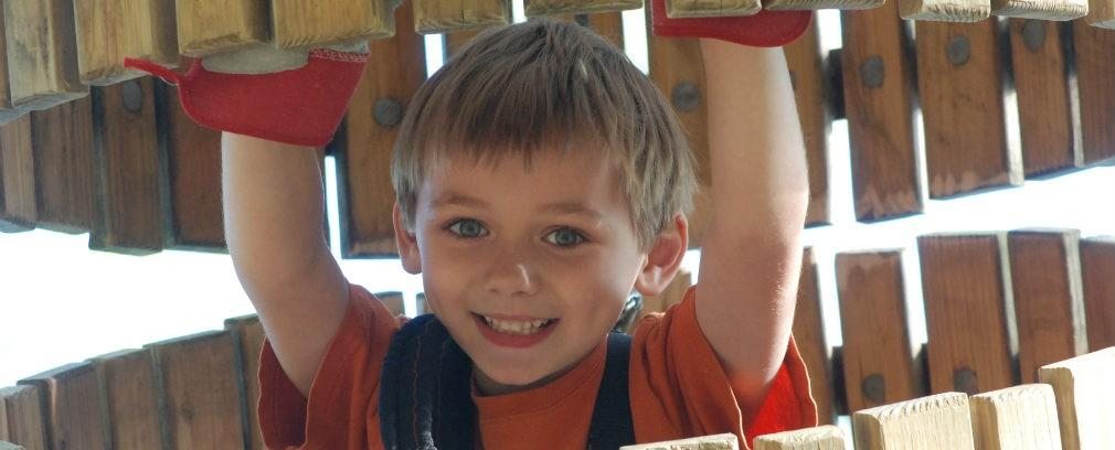 Little boy is all smiles on the Tree Venture obstacle course
